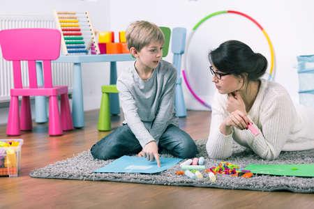 Magántanár és kis fiú tanulás játszani otthon