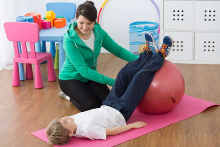 gym ball: Physiotherapist and boy lying on foam mattress, exercising on gym ball