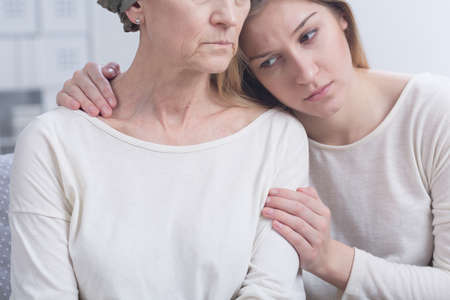 sick leave: Sad girl embracing cancer woman Stock Photo