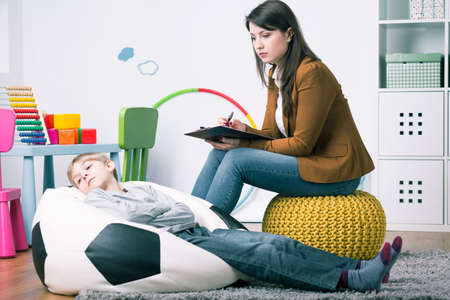 misbehaving: Misbehaving boy lying on sack chair during home session with psychologist