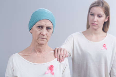 sick leave: Tired cancer woman with headscarf and girl with pink ribbon holding hand on her arm Stock Photo