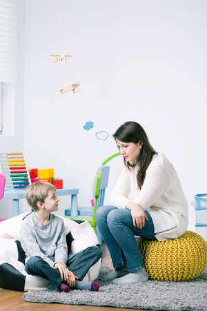 babysitter: Young babysitter and boy sitting together in child room