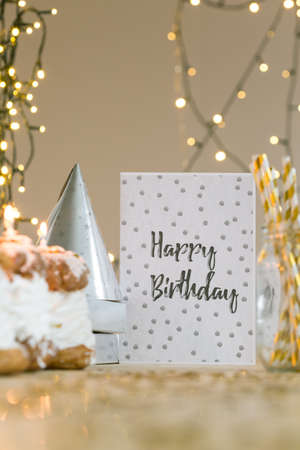 birthday decoration: Birthday card lying on table with golden decoration