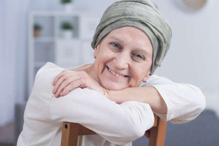 Cancer woman with headscarf sitting on chair, smiling