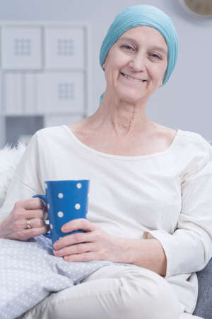 inner strength: Positive cancer woman with headscarf, sitting,holding cup