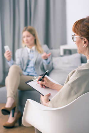 work addicted: Psychologist making notes and woman addicted to work with cellphone Stock Photo