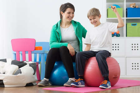 faulty: Boy and his instructor exercising on gym balls