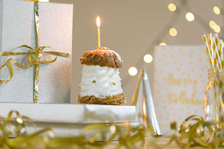 cream puff: Cream puff with candle, present and birthday card lying on table with golden decoration