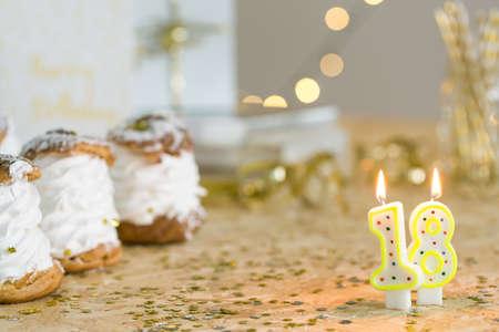 Nummer achttien verjaardagskaars en slagroomsoesjes op tafel met gouden decoratie