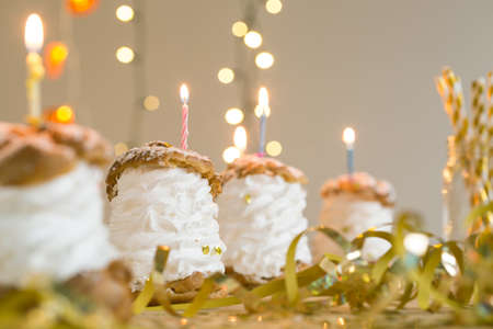 birthday decoration: Birthday cream puffs with candles lying on table with golden decoration