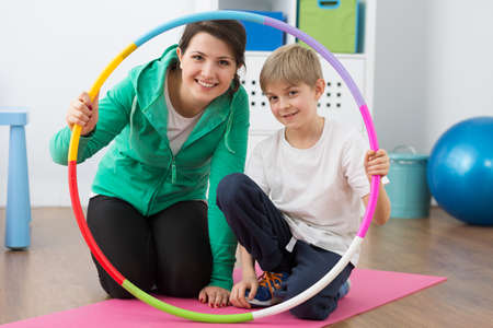 boy lady: Happy physiotherapist and boy holding hoop