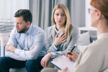 a marriage meeting: Sad wife and her husband during meeting with marriage counselor Stock Photo
