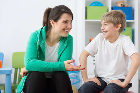 faulty: Happy physiotherapist and small boy sitting in rehabilitation room