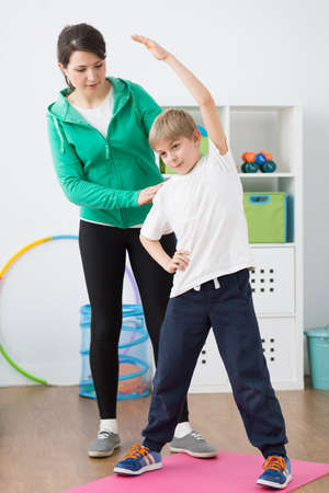 faulty: Boy exercising in rehabilitation room with physiotherapist