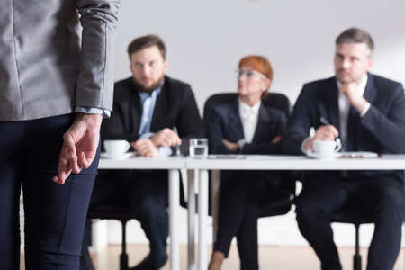 company job: Woman crossing fingers back view and three businesspeople