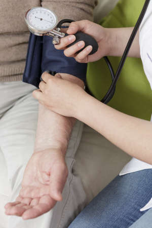 high blood pressure: Doctor is checking her patients blood pressure Stock Photo
