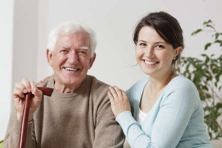 Adult daughter is hugging her old father Stock Photo