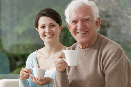 adult offspring: Grandfather and granddaughter are drinking tea together