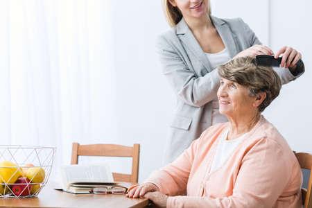Horizontal view of granddaughter combing grandmas hair