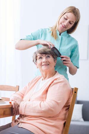Young female caregiver doing senior woman's hair Stockfoto