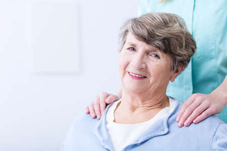 supported: Smiling senior woman supported by caregiver or nurse