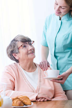 second breakfast: Caregiver giving senior woman coffee and croissant Stock Photo