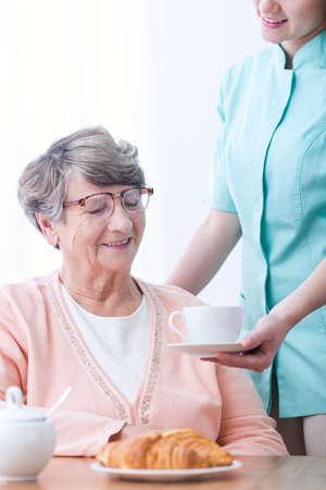 second breakfast: Senior woman eating croissant for second breakfast