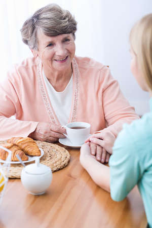 home keeping: Young female carer keeping company senior woman