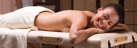 massage table: Panorama of smiling woman lying on massage table Stock Photo