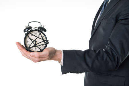 company person: Man in suit holding alarm clock, standing on white background, close up.