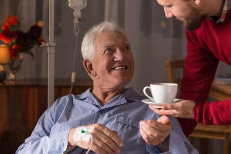 Férfi gondozó segítő gyógyíthatatlan beteg idősebb férfi