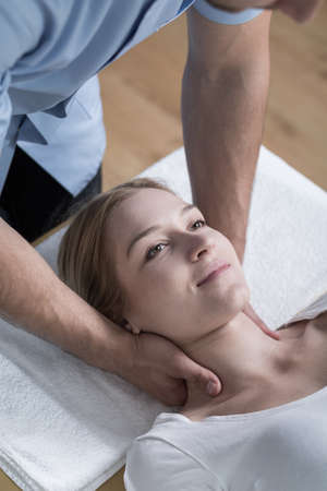 sprained joint: Physiotherapist stabilizing young womans neck with his hands