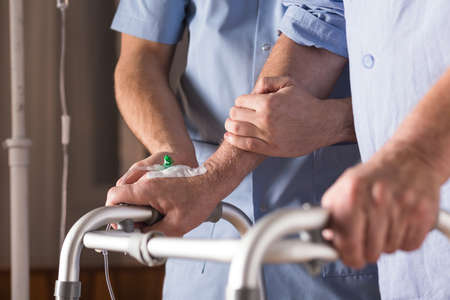 enfermera con paciente: Primer plano de la persona con discapacidad caminar con ayuda