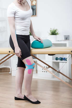 sprained: Girl with sprained knee trying to walk Stock Photo