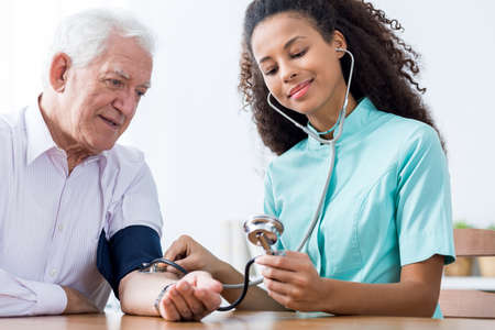 Photo of old male and nurse taking blood pressure Stock Photo