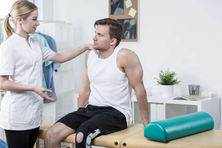 sprained joint: Injured handsome sportsman and young female physiotherapist Stock Photo