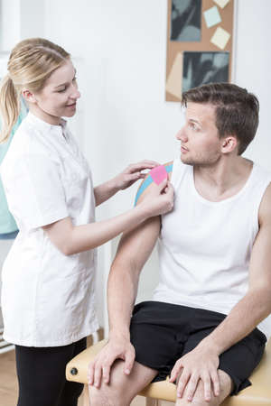 sprained joint: Physiotherapist applying kinesio tape on mans shoulder