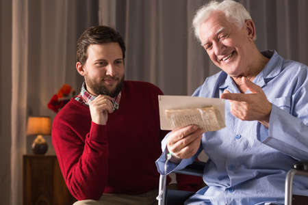 nearness: Carer assisting disabled senior man at home