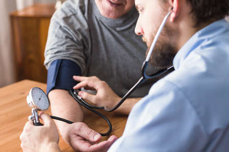 Hypertensieve senior man tijdens bloeddrukmeting Stockfoto