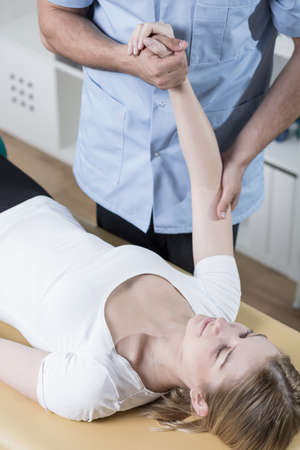 sprained joint: Young woman undergoing rehabilitation of injured arm Stock Photo