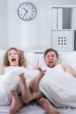 enamorados en la cama: Pareja sorprendida acostada en la cama y gritando