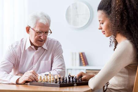 Obraz emerytowany mężczyzna gra w szachy z prywatnym opiekunem