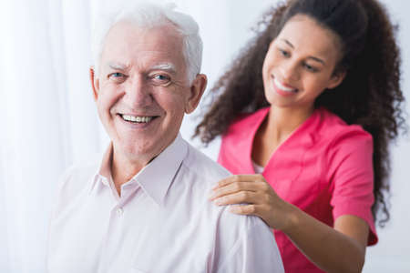 positive: Picture of happy positive senior and afroamerican caregiver