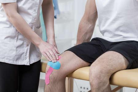 sportsman: Fisioterapeuta haciendo kinesiología grabar en el esguince de rodilla Foto de archivo