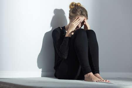 mujer triste: Desglosado chica solitaria joven con la depresión