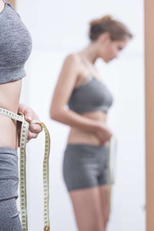 anorexia: Girl with anorexia checking her waist circuit