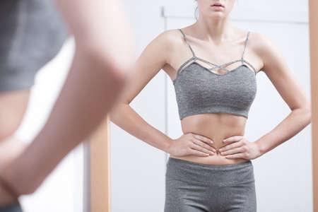 skinny: chica flaca que sostiene la cintura mirando en el espejo Foto de archivo