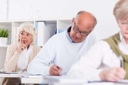 hombre escribiendo: El estudiante está pensando qué escribir en su examen Foto de archivo