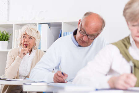old writing: Student is thinking what to write on her test Stock Photo