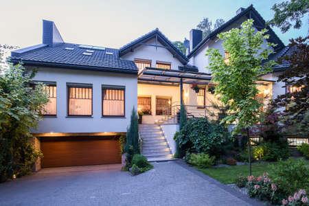 Velký rodinný dům ve večerních hodinách s rozsvícenými světly